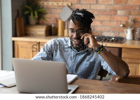 Happy young african american businessman talking on cellphone while working on computer distantly at home. Smiling 30s multiracial man in glasses consulting client by phone call, multitasking concept. Stock photo ©