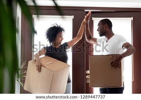 Happy young african american couple tenants give high five celebrate moving day in own house hold boxes, excited black family first time buyers owners in new home, mortgage goals, relocation concept