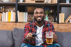 happy young african american man holding glass of beer and remote controller while sitting on sofa at home