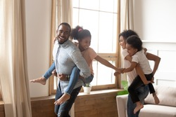 Happy young african American parents have fun with little kids carry them on back chasing each other, smiling black family playing together at home, biracial children piggyback mom and dad laughing