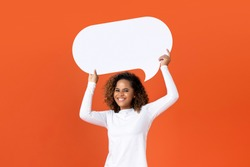 Happy young African American woman in plain white long sleeve t-shirt holding empty speech bubble isolated on orange  background