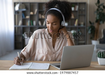 Happy young african american woman in wireless headphones listening educational online lecture, writing down important information. Smart mixed race student involved in online study by video zoom call