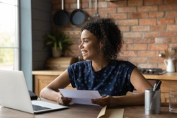 Happy young African American woman sit at table in home office read good news in post paper correspondence. Smiling biracial female excited with pleasant message or notice in paperwork letter.