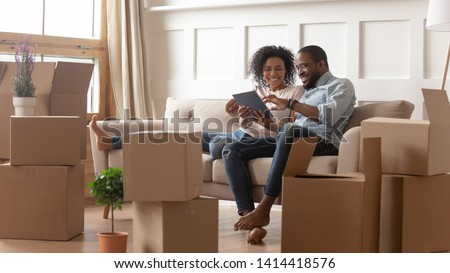 Happy young african couple use digital tablet discuss interior design renovation ideas sit on sofa on moving day, black new house renters owners tenants relax on couch with boxes having fun online #1414418576