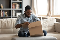 Happy young african ethnicity male client sitting on sofa at home, opening huge carton box, satisfied with fast delivery service. Smiling man unboxing parcel, glad getting order from internet store.