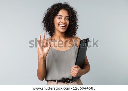 Happy young african woman casually dressed standing isolated over gray background, holding a notepad, ok gesture