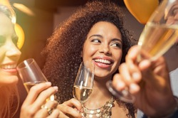 Happy young african woman holding wine glass with friends at party. Portrait of beautiful black girl enjoying new year's eve with friends. Cheerful smiling woman drinking champagne at evening party.