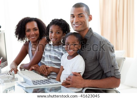 Happy young Afro-American family working with a computer at home