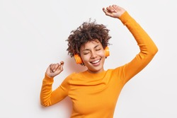 Happy young Afro American woman carried away with music dances carefree with arms raised keeps eyes closed wears stereo headphones on ears dressed in orange jumper isolated over white background
