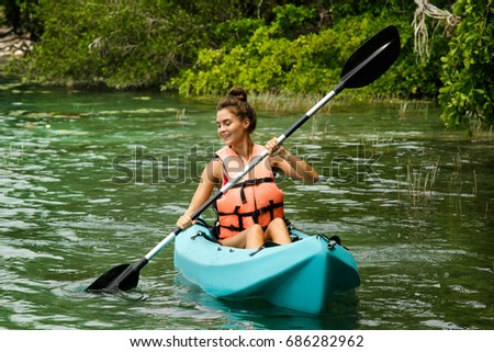Happy young and beautiful woman kayaking in on the lake #686282962