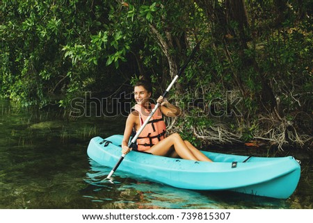 Happy young and beautiful woman kayaking in on the lake #739815307
