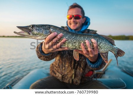 Happy young angler holds the pike fish (Esox lucius) sitting in a boat. Outdoor fishing activity #760739980