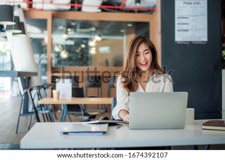 Happy young asian businesswoman sitting on her workplace in the office. Young woman working at laptop in the office.