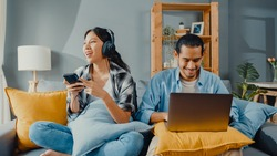 Happy young asian couple activity man use laptop computer work relax enjoy with women wear headphones use smartphone listen music at sofa in living room at house. Young married work from home concept.