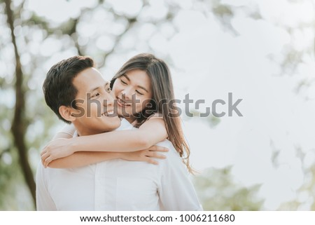 Happy young Asian couple in love having a good time and embracing in the park