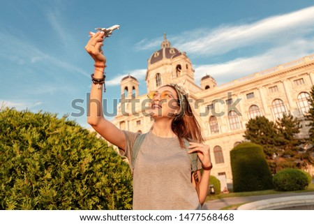 Happy young Asian girl with a toy airplane posing against the backdrop of a historic building in a European city. Travel and Air tourism transport Concept #1477568468