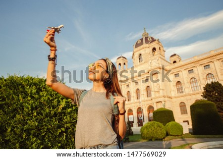 Happy young Asian girl with a toy airplane posing against the backdrop of a historic building in a European city. Travel and Air tourism transport Concept #1477569029