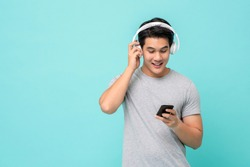 Happy young Asian man wearing wireless headphones listening to music from smartphone studio shot isolated on light blue background