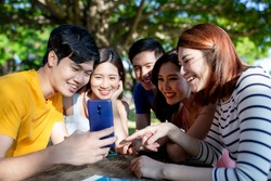 happy young asian students share an interesting APP on smartphone on campus