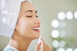 Happy young Asian woman enjoying applying refreshing soothing treatment lotion on her face with cotton pad