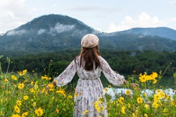 Happy young Asian woman enjoying in yellow flower field at sunset.