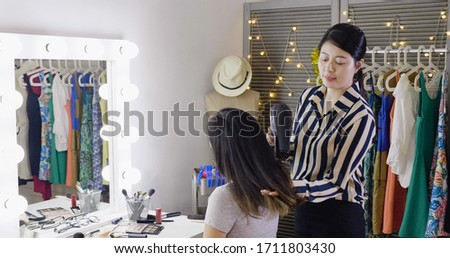 Happy young asian woman entertainer and hairdresser with fan making hot styling at dressing place. girl celebrity sitting at vanity table in makeup room while stylist using hair drying blowing.