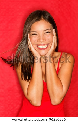 Happy young asian woman excited smiling cheerful holding head in joy. Beautiful multiracial Asian / Caucasian girl candid on red background.