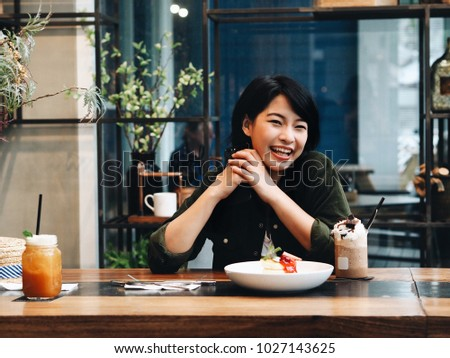 Happy young Asian woman food blogger joyful with food in restaurant.