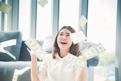 Happy young asian woman holding dollar money and throw in the air celebrate happiness dance wealth lottery money rain drop. Winner Success business woman throw cash flow Happy money smiling face
