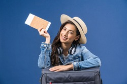 Happy young Asian woman holding passport with boarding pass and presenting on blue color background, earphone and baggage, holiday and travel concept