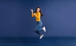 Happy young Asian woman in colorful yellow color casual clothes jumping and presenting to copy space on blue color background, lifestyle and leisure, travel and tourist, travel and vacation concept