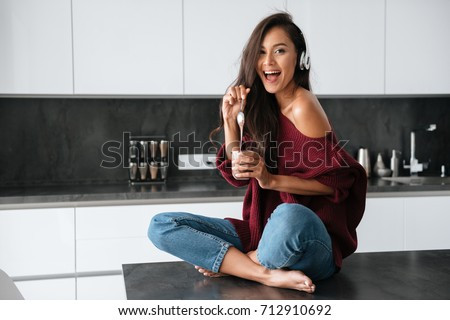 Happy young asian woman in headphones eating dessert with a spoon from a jar in a kitchen