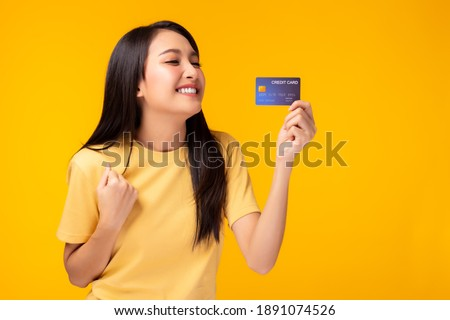 Happy young asian woman showing plastic credit card and looking at credit card with happy Standing over yellow background Customer girl get satisfied of credit card service with smile on face