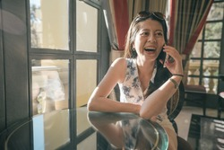Happy young asian woman tourist using cell phone in hotel lobby. vintage style photo of sunshine through window on girl face. cheerful lady traveler talking on smart phone and laughing loudly.