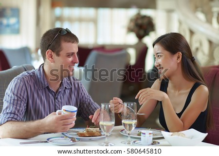 Happy Young Asian Woman WIth European Young Male Friend in the Restaurant #580645810