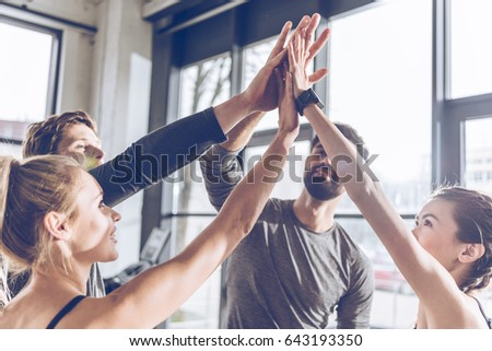 Happy young athletic people in sportswear giving high five in gym #643193350