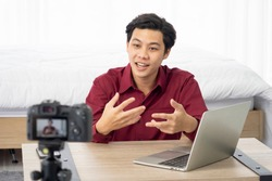 Happy young attractive Asian influence male vlogger talking and smile for live streaming, broadcast with internet subscribers. Social media people , content maker, e-commerce concept. working at home.