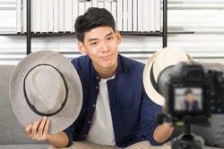 Happy young attractive Asian male blogger or vlogger present hat on live streaming, broadcast with internet subscribers. Social media influence people, content maker, e-commerce, Work at home concept.