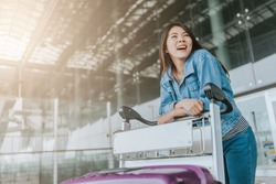 Happy young attractive Asian woman passenger with luggage trolley walking through an airport