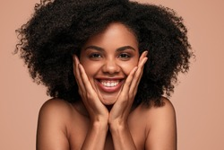 Happy young bare shouldered black female with smooth skin touching face and looking at camera on orange background