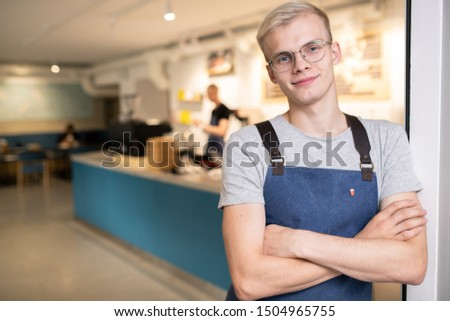 Happy young barista in eyeglasses, grey t-shirt and blue apron crossing his arms on chest while standing in front of camera in cafe
