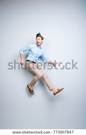 Happy, young, bearded, attractive handsome man in shirt, pants  jumping in air over grey background #773007847