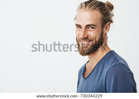 Happy young bearded guy with fashionable hairstyle and beard looking at camera, brightfully smiling with teeth, being happy about day off on work.