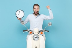Happy young bearded man guy in casual light shirt driving moped isolated on pastel blue wall background. Driving motorbike transportation concept. Mock up copy space. Hold clock, doing winner gesture