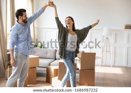 Happy young bearded man holding hand, twisting joyful wife in new living room near carton boxes. Excited married couple celebrating moving day in apartment house, dancing to energetic music.
