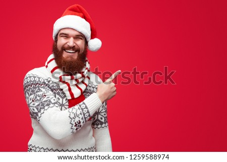 1cfb6bd3ec7d2 Happy young bearded man in christmas clothes pointing away at copyspace  isolated over red background.