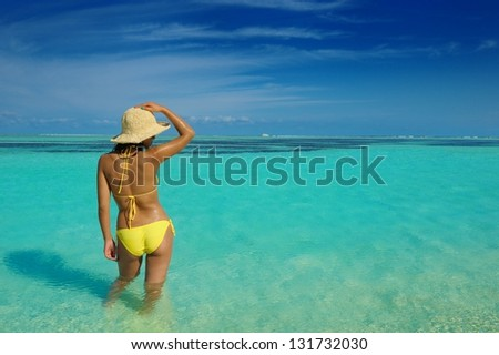 happy young beautiful asian woman relax on sand at tropical beach with cristal clear sea in background