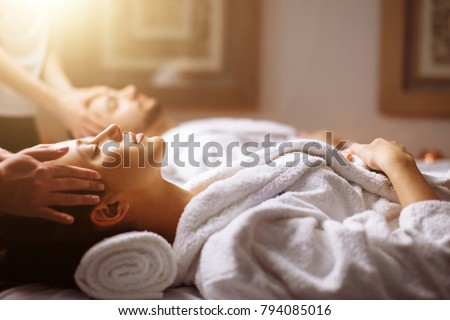 happy young beautiful couple enjoying head massage at the spa #794085016
