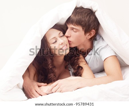 happy young beautiful couple under the blanket in bed at home