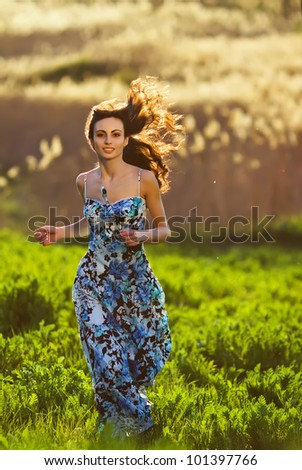 happy young beautiful girl outdoor on the field,running